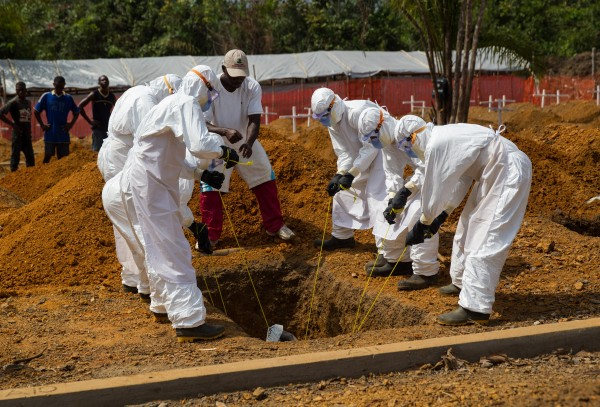 A burial team is lowering the body of a suspected Ebola victim into a grave in a new cemetery. The burial site was opened on 23 December 2014 in the Disco Hill district to ensure that Ebola victims from Monrovia and the surrounding counties could be buried in a safe and dignified way. Photo: UNMEER/Martine Perret